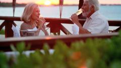 Caucasian seniors enjoying romantic dining on vacation - stock footage