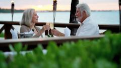 Happy Caucasian senior couple dining at sunset at beachfront hotel Stock Footage