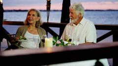 Senior Caucasian couple dining at a tropical resort hotel Stock Footage