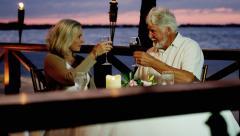 Caucasian seniors enjoying romantic sunset dining on vacation - stock footage