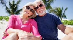 Caucasian senior couple in bright clothing enjoying a beach vacation - stock footage