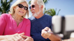 Retired Caucasian couple taking a selfie at a beach resort Stock Footage
