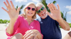 Retired Caucasian couple smiling for social media at beach resort Stock Footage