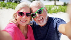 Senior Caucasian couple on a beach taking a selfie - stock footage