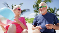 Retired Caucasian couple having fun outdoor with a beach ball - stock footage
