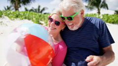 Happy retired Caucasian seniors on a beach with a beach ball - stock footage