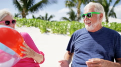 Caucasian senior couple playing with beach ball Stock Footage