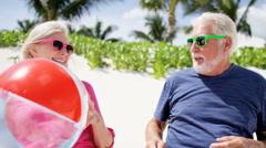 Caucasian senior couple on a tropical beach with beach ball - stock footage