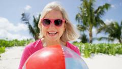 Portrait of a Caucasian senior female playing with beach ball - stock footage