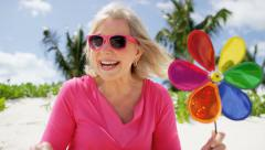 Caucasian senior female on a tropical beach with a toy pinwheel - stock footage
