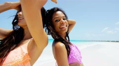 Young multi ethnic girlfriends wearing a bikini on beach - stock footage