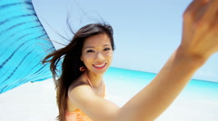Asian Chinese girl with scarf wearing tropical beach swimwear - stock footage