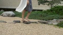 Barefoot woman walks through rock garden Stock Footage