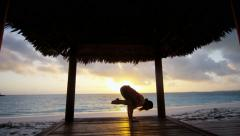 Sunrise silhouette of young girl practicing yoga Stock Footage