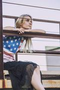 Female model sitting at a railing in a t-shirt with the American flag - stock photo