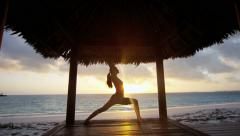 Girl in silhouette practicing yoga outdoor Stock Footage