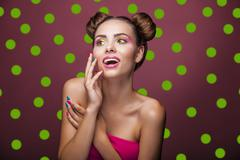 Beautiful fashion model girl with bright makeup and funny hair on a pink back Stock Photos