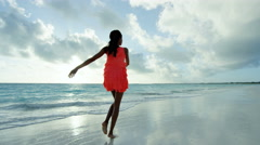 African American girl in red dress barefoot on ocean sand - stock footage
