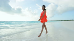 Luxury resort with ethnic female in red dress on sand barefoot - stock footage