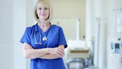 Portrait of professional senior Caucasian female hospital nurse wearing scrubs - stock footage