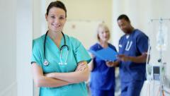 Portrait of confident Caucasian female young nurse in medical centre corridor - stock footage