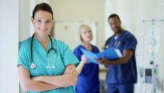 Portrait of confident young Caucasian female medical center nurse wearing scrubs - stock footage