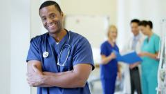 Portrait of confident African American male young nurse in hospital corridor - stock footage