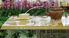 Decorative fountain. Jet of water pours from a teapot into a cup. Stock Footage