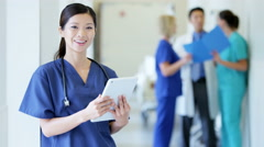 Portrait of Asian American female nurse working on technology in medical centre Stock Footage