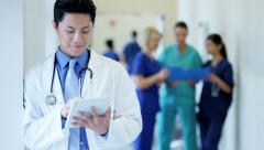 Chinese American male young doctor working on tablet technology in hospital - stock footage