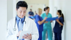 Asian Chinese male young doctor working on tablet technology in medical center - stock footage