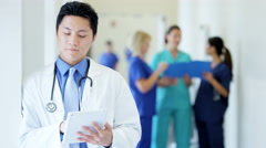 Asian American male young doctor working on tablet technology in medical centre - stock footage