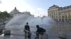Boys and girls relaxing at the fountain in Karlsplatz, Munich Stock Footage
