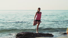Young female does yoga on the beach slow motion Stock Footage