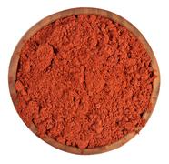 Ground paprika in a wooden bowl on a white - stock photo
