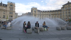 Young people relaxing near the fountain of Karlsplatz, Munich Stock Footage
