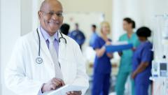 Portrait of African American male doctor using tablet technology in hospital - stock footage