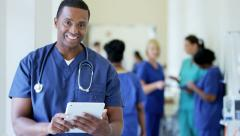 Portrait of African American male nurse working on technology in medical centre Stock Footage