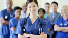 Portrait of confident Chinese Asian female nurse and team of staff in hospital Stock Footage