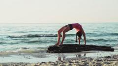 young female does gymnastics on the beach slow motion - stock footage