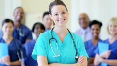 Portrait of confident Caucasian young female nurse and team of staff in hospital Stock Footage