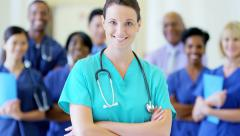Portrait of confident Caucasian young female doctor and team in medical center Stock Footage