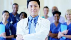 Portrait of confident Asian American male doctor and team of staff in hospital - stock footage