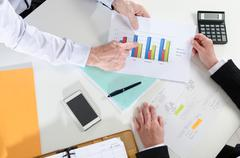 Businesspeople having a discussion about  financial report - stock photo