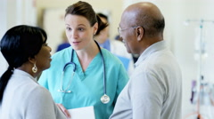Caucasian female doctor consult with African American couple in medical center Stock Footage