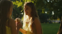 Twin Girls are Eating Ice Cream at Park - stock footage
