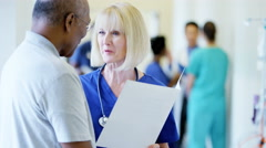 Caucasian female staff consult with African American male senior in hospital - stock footage