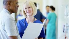Caucasian female nurse consult with African American male in medical centre Stock Footage