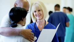 Caucasian female staff consult with African American couple in medical center - stock footage
