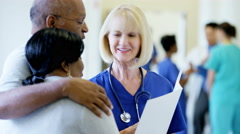 Caucasian female staff consult with African American senior couple in hospital - stock footage